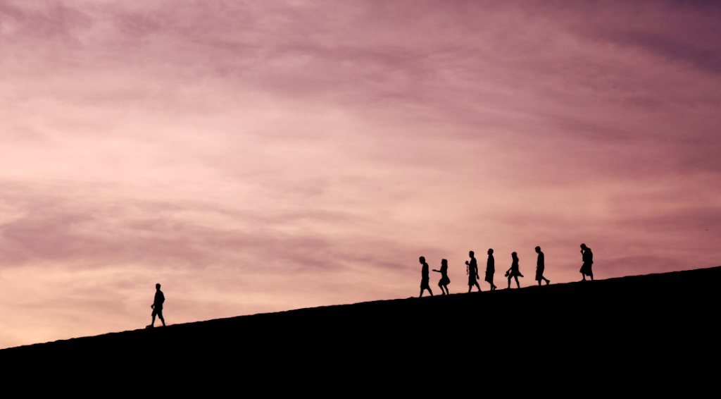 One man walking ahead while seven people follow him in a fair distance.