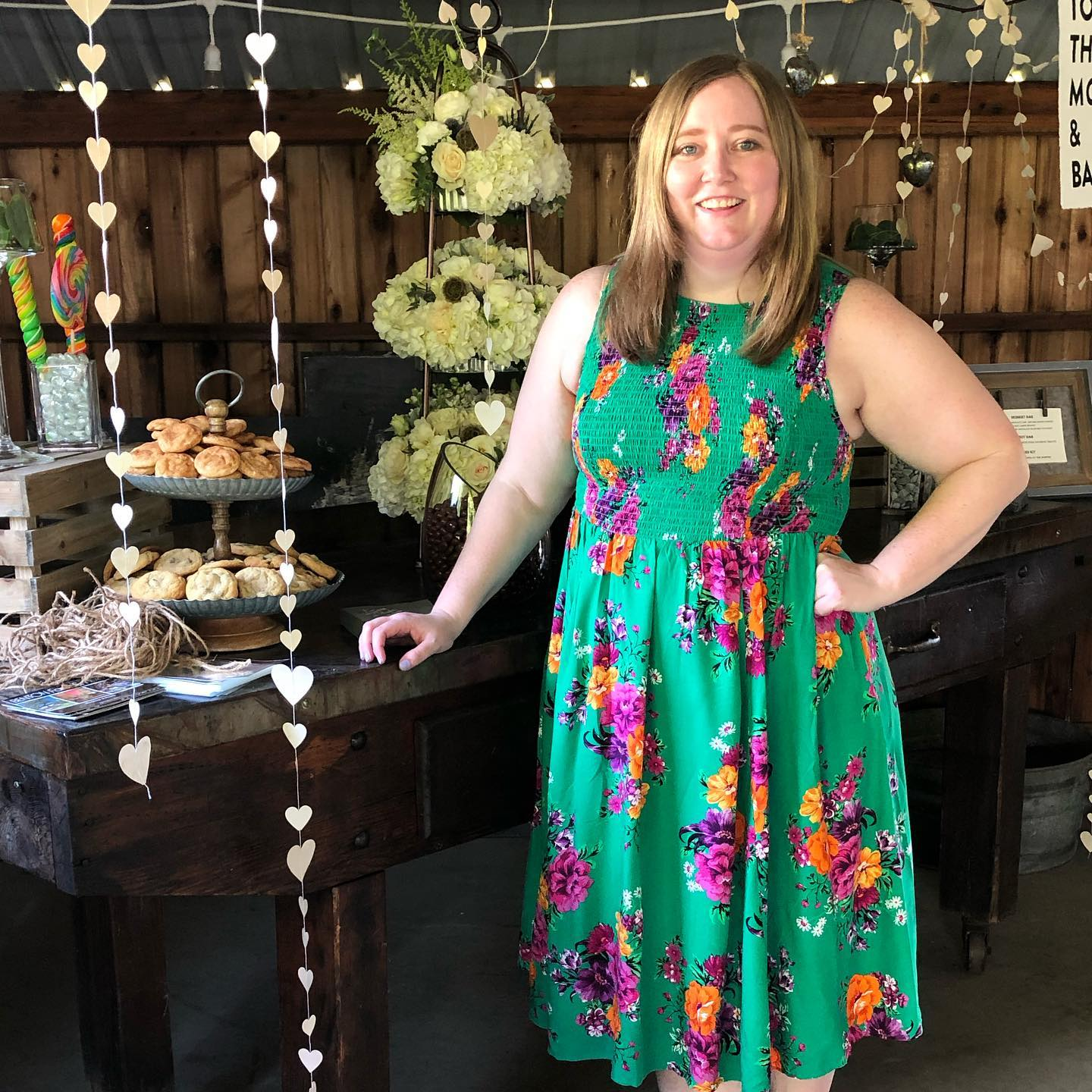 Kate Johnson in a green floral dress standing in front of a banquest table.